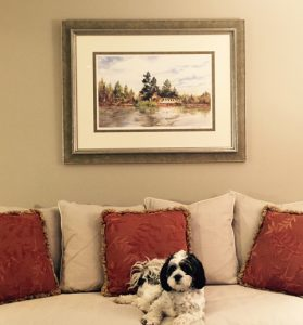 Dog sitting on couch under a painting
